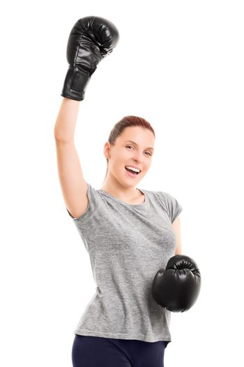 A portrait of a beautiful fit young girl with boxing gloves cheering, isolated on white background.