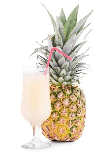 Uncut pineapple fruit next to a glass of juice with a straw, isolated on white background.