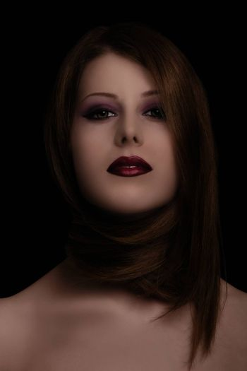 Low key sensual, make up, and beauty portrait of a woman with her hair around her neck on black background.