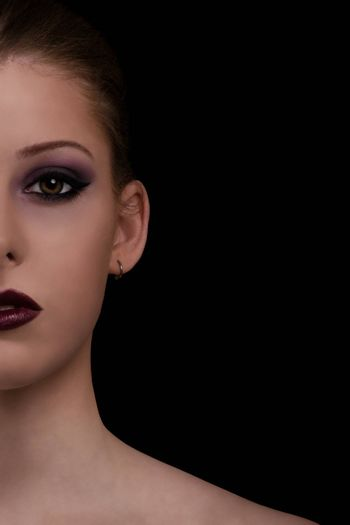 Low key beauty portrait of a young woman with sensual make up on, isolated on black background.