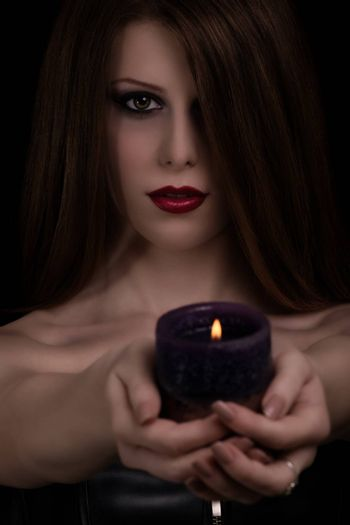 Low key portrait of a mystical beautiful goth girl holding a candle, isolated on black background.