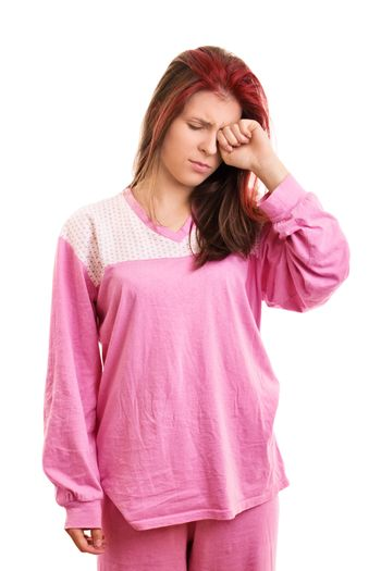 Leave me alone, I'm so sleepy. A portrait of a sleepy beautiful young girl in pink pajamas rubbing her eye, isolated on white background.