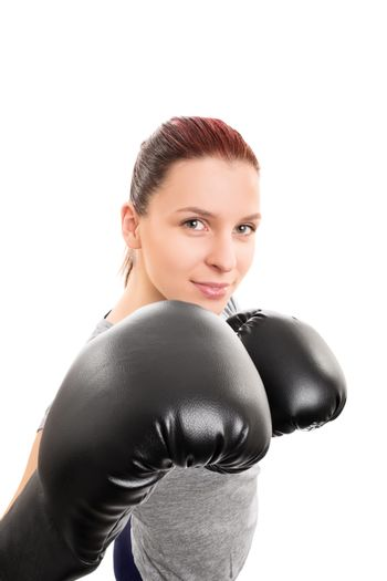 Close up shot of a smiling beautiful young girl with boxing gloves, isolated on white background.