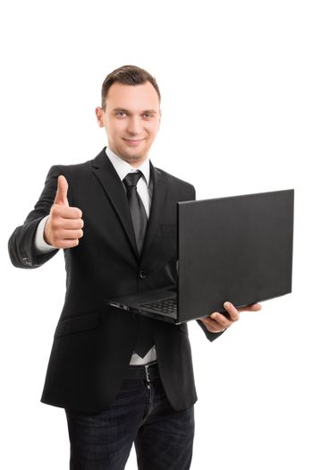 A portrait of a young businessman in a suit holding a laptop and giving thumbs up, isolated on white background.