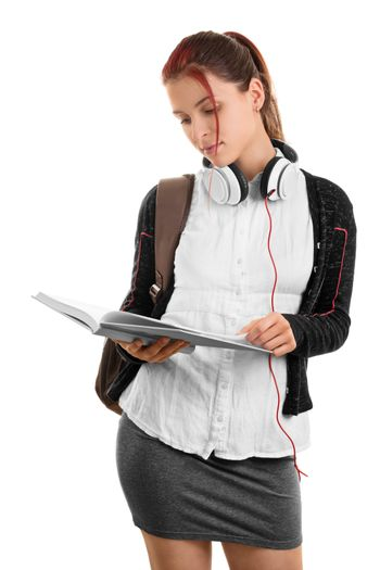 Going through my notes while the music is off. Beautiful young student in uniform with a backpack holding an open notebook, isolated on white background.