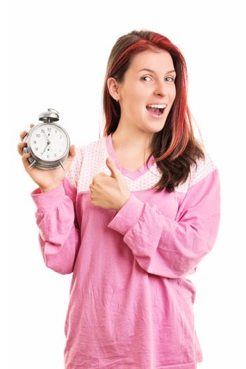 When timing is right. Smiling young girl in pink pajamas holding an alarm clock and giving thumbs up, isolated on white background.