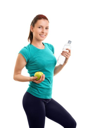 A portrait of a beautiful fit young girl holding an apple and a bottle of water, isolated on white background. Water and snack after my workout.