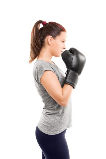 A profile of a beautiful young girl with boxing gloves holding her guard up, isolated on white background.