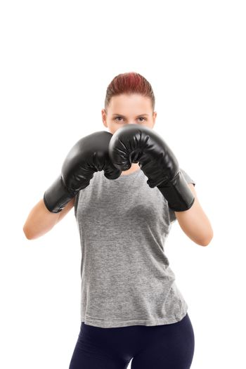 A portrait of a beautiful young girl with boxing gloves in a blocking stance, isolated on white background.