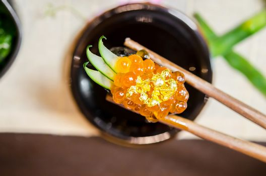 Wooden chopsticks tongs Gunkan Maki Sushi with salmon caviar (Ik