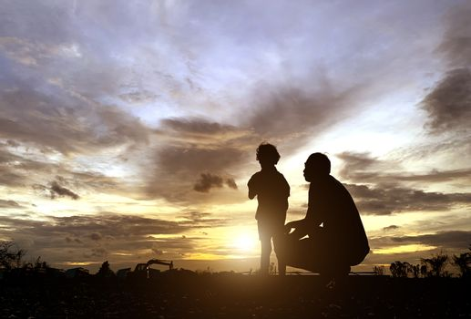 The silhouette of the father and son who enjoyed the sunset for