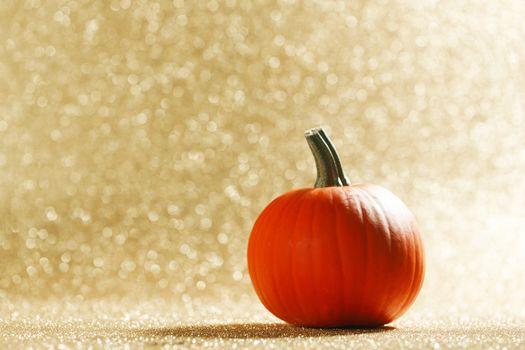 Pumpkin on glittery background