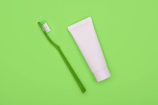 Close up one white toothpaste tube and plastic toothbrush on natural green background, flat lay, elevated top view, directly above