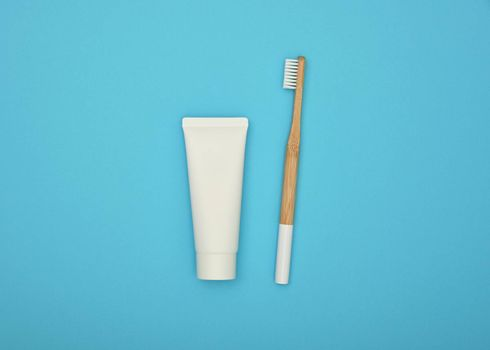 Close up one white toothpaste tube and natural wooden bamboo toothbrush on blue background, flat lay, elevated top view, directly above
