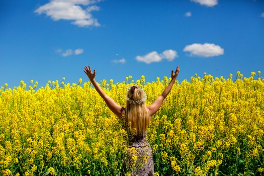 Woman in a field of golden yellow flowers Canola