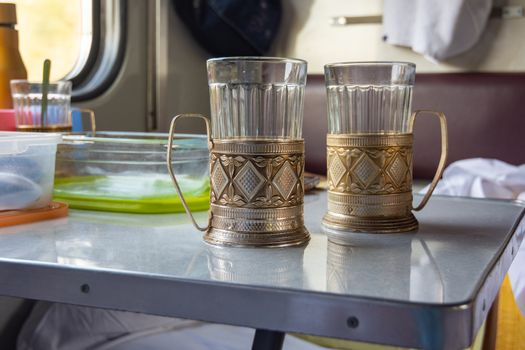 Empty glasses in metal cup holders stand on a table in a train compartment