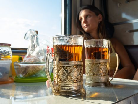 On the table in the compartment of the train are glasses with tea in metal cup holders, in the background the girl looks out the window