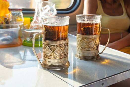 On the table in the train compartment are glasses with tea in metal cup holders.
