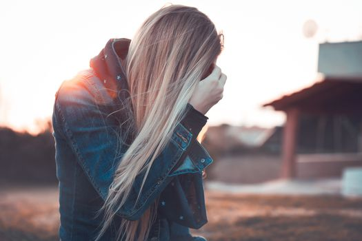 Blond woman wearing jeans jacket standing outdoors in mild sunset light, autumn fashion of youth, urban lifestyle concept