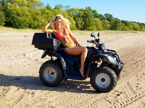 attractive woman in bikini and sunglasses with long blonde hair is sitting on the quad bike, sunny day on the beach