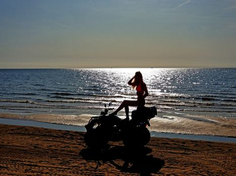 silhouette of a woman with long blond hair sitting on a quad bike, sunny day at the beach. Shooting against the sun