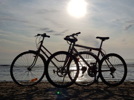 Silhouettes two bicycles parked in the sand beach on a bright sunny summer day. Shooting against the sun