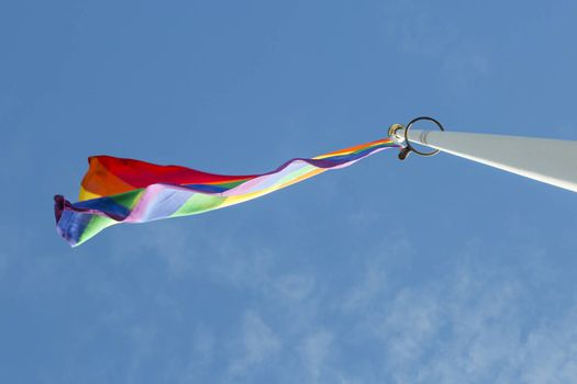 Rainbow Flag waving in the wind with a partly cloudy sky.