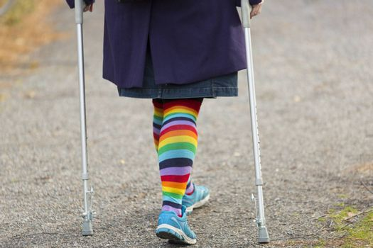 Female with Rainbow Leggings and crutches Walking.