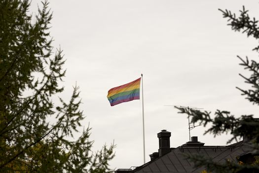 Rainbow Flag waving in the wind on Roof with a cloudy sky.