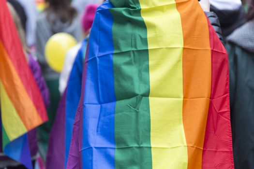 Person Carrying Rainbow Flag over Sholders in Pride Parade.