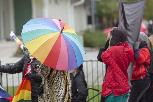 Person Carrying Rainbow Umbrella in Pride Parade.