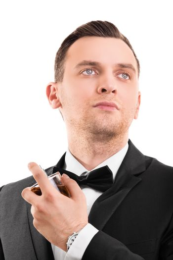 A portrait of a young handsome man in a suit using a perfume, isolated on white background.