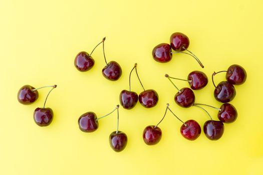 ripe fresh cherry on a yellow background