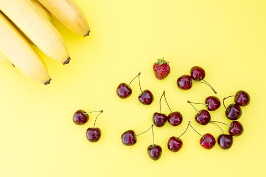 ripe fresh cherry, strawberry and bananas on a yellow background