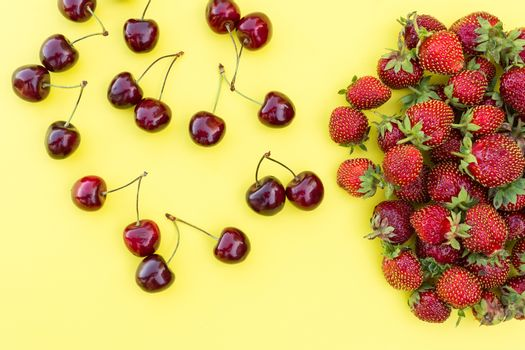 fresh strawberries and cherries on a yellow background