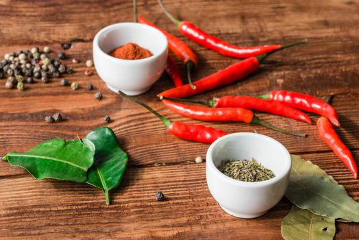 Different condiment in white bowls or scattered on kitchen table.