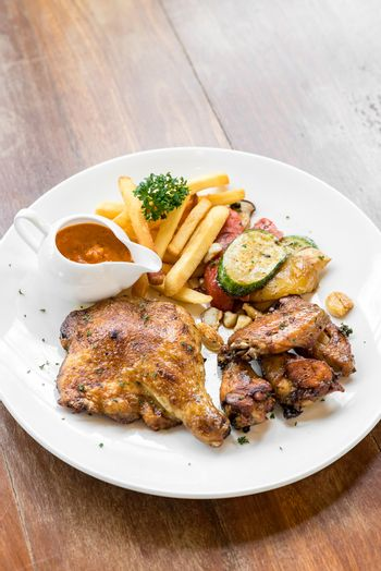 grilled chicken peri peri, BBQ Portuguese groumet griled cuisine, with fries and grilled vegetable.