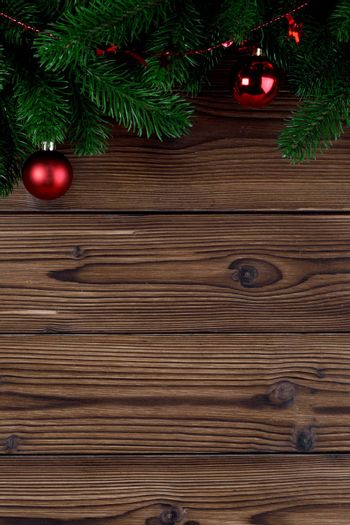 Christmas decoration on wooden background, fir tree branch, red baubles