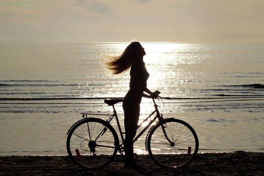 silhouette of a girl with long hair on a bicycle riding on the sand by the sea. Against the background of a small surf of the Baltic Sea. Shooting against the sun. Reflection of the sun on the surface of the water.