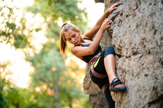 Beautiful Woman Climbing on the Rock in the Mountains. Adventure and Extreme Sport Concept