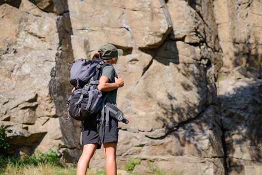 Young Beautiful Woman Hiker with Big Backpack on the Rock Background. Adventure and Travel Concept