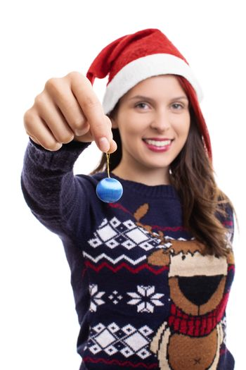 Close up shot of a beautiful smiling girl in a festive sweater with a Santa`s hat on, holding a Christmas decoration, isolated on a white background.