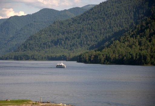 Passenger ship sailing on the lake surrounded by high mountains overgrown with coniferous forest. Teletskoye Lake, Altai, Siberia, Russia.