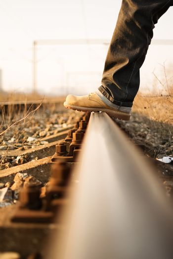 Time for a new journey. Man's foot stepping over train tracks.