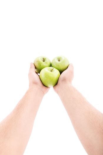 Stretched out male hands offering green apples, isolated on white background.