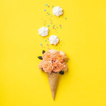 Ice cream cone with pink roses and merengues on yellow background. Summer minimal concept. Flat lay.