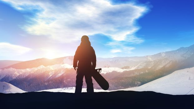 Silhouette of a snowboarder on a background of sunlit snowy mountains.