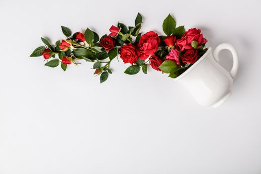 Creative layout made of coffee or tea cup with red roses on white background
