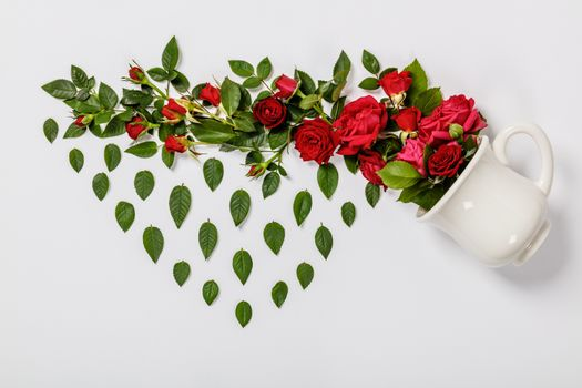 Flowers composition. Creative layout made of coffee or tea cup with red roses on white background, flat lay
