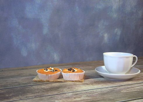 A cup of tea on a saucer and two cupcakes on a textile napkin. Close-up.